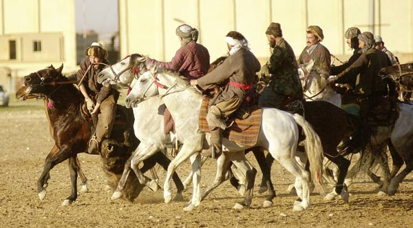 A game of buzkashi in Mazar-e-Sharif, Afghanistan. Sometimes in teams, buzkashi players fight to drag a goat or calf carcass to the goal.